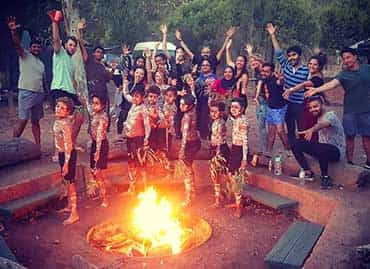 Students and aboriginal children posing around the camp fire