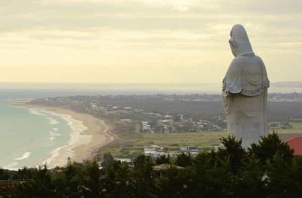 A statue overlooking a city and the beach
