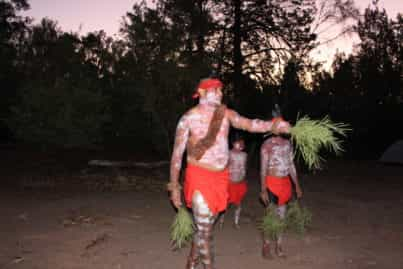 Men covered in white paint wearing red head piece and red cloth holding leaves