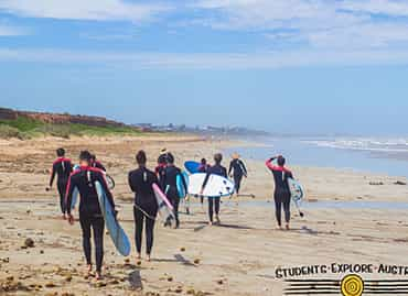 Students with surfboards walking on the beach
