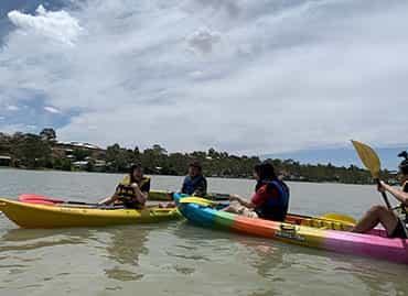 Students on kayaks paddling in the water