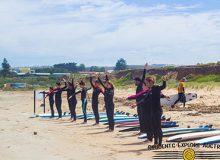 Students stretching at the beach with surfboards