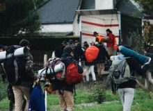Students with camping backpacks walking